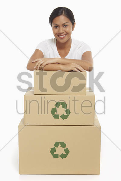 cheerful woman resting her arms on a stack of cardboard boxes stock photo