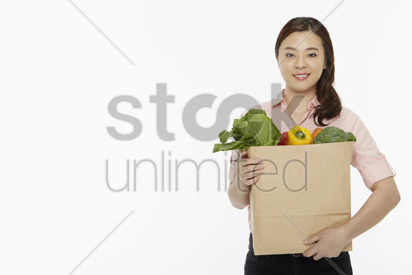 cheerful woman with a bag of groceries stock photo