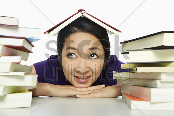 cheerful woman with a book over her head stock photo