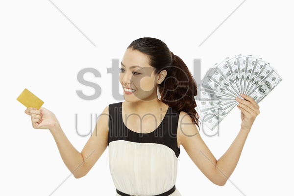 cheerful woman with a credit card and cash stock photo