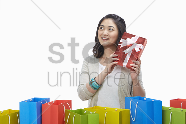 cheerful woman with a red gift box at her ear stock photo