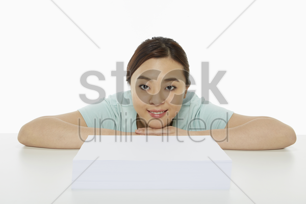 cheerful woman with a stack of papers in front of her stock photo