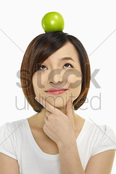 cheerful woman with an apple on her head stock photo