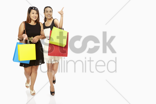 cheerful women carrying paper bags and smiling stock photo