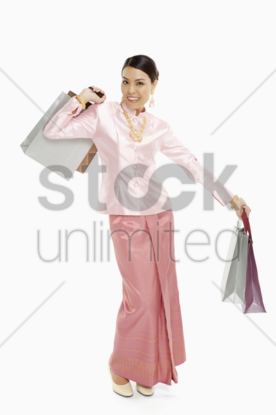 cheerful women in traditional clothing carrying paper bags stock photo