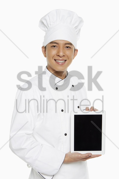 chef holding up a digital tablet stock photo