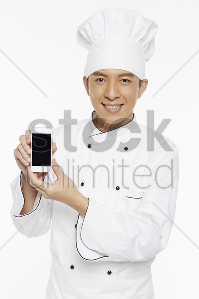 chef holding up a mobile phone stock photo