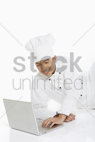 chef lying on the floor, using a laptop stock photo