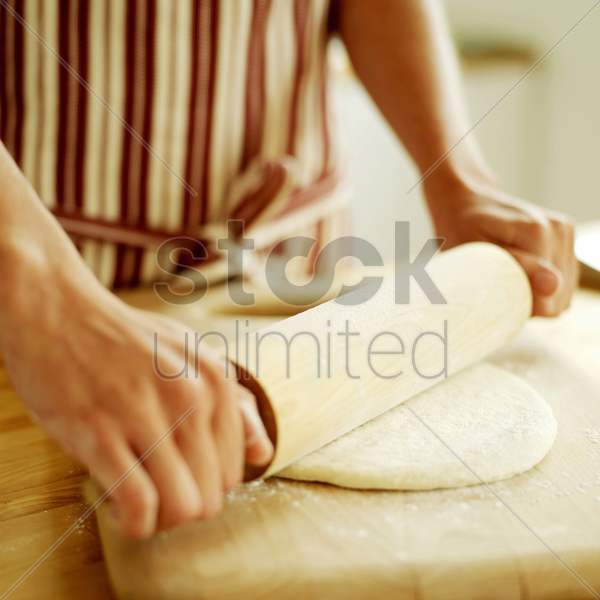 chef rolling out pizza dough with a wooden rolling pin wearing a red stripy apron stock photo