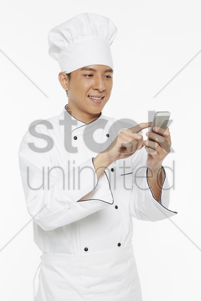 chef sending a text message on his mobile phone stock photo