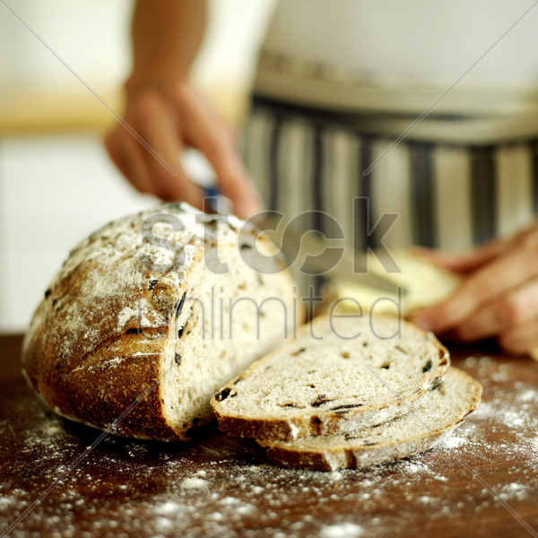chef slicing country olive bread stock photo