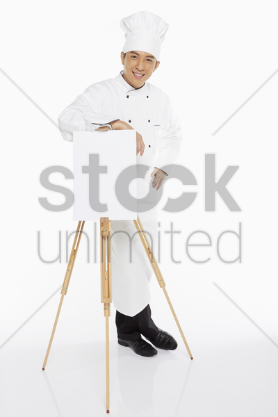 chef standing behind an easel, smiling stock photo