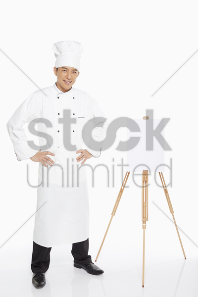 chef standing beside an easel stock photo