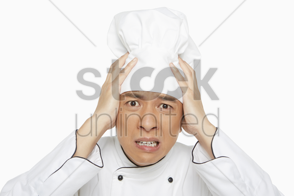 chef touching his forehead stock photo