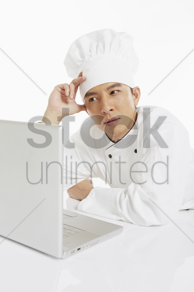 chef using a laptop, looking stressed stock photo