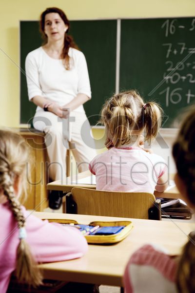 children and teacher in the classroom stock photo