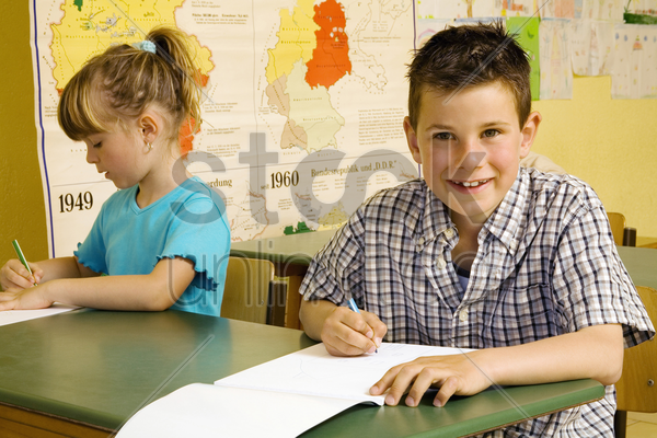 children colouring in the classroom stock photo