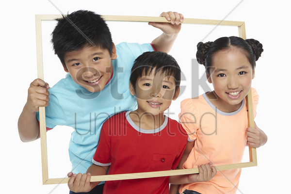 children holding up a wooden picture frame, smiling stock photo