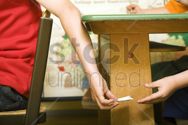 children passing note under the table stock photo