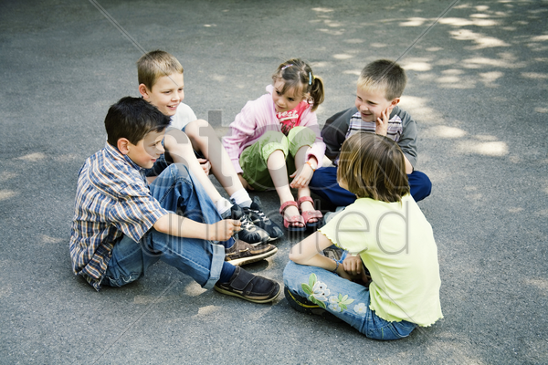 children sitting in a circle playing stock photo