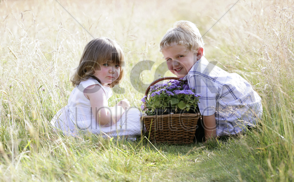 children with a basket of flowers stock photo