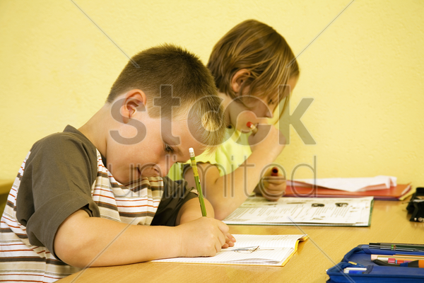 children writing in the classroom stock photo