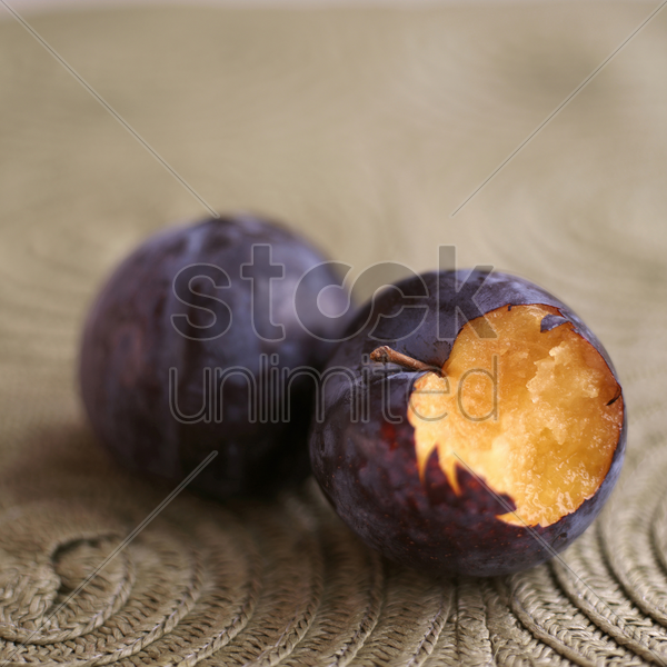 close up of a bitten plum next to another plum stock photo