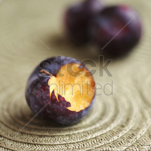 close up of a bitten plum stock photo