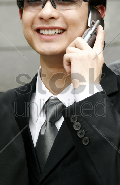 close-up of a man with sunglass talking on the hand phone stock photo