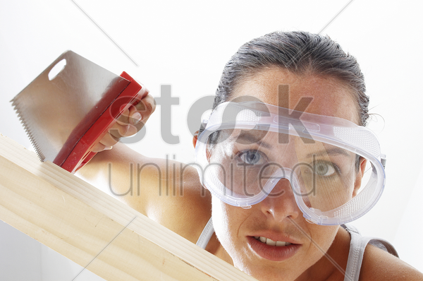 close-up of a woman with goggles sawing a wood stock photo