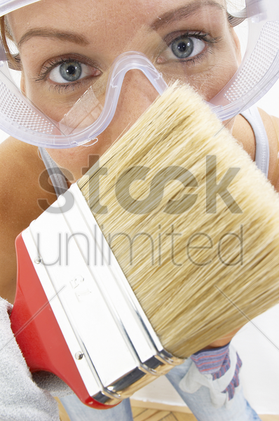 close-up of a woman with goggles using a brush to brush the camera stock photo