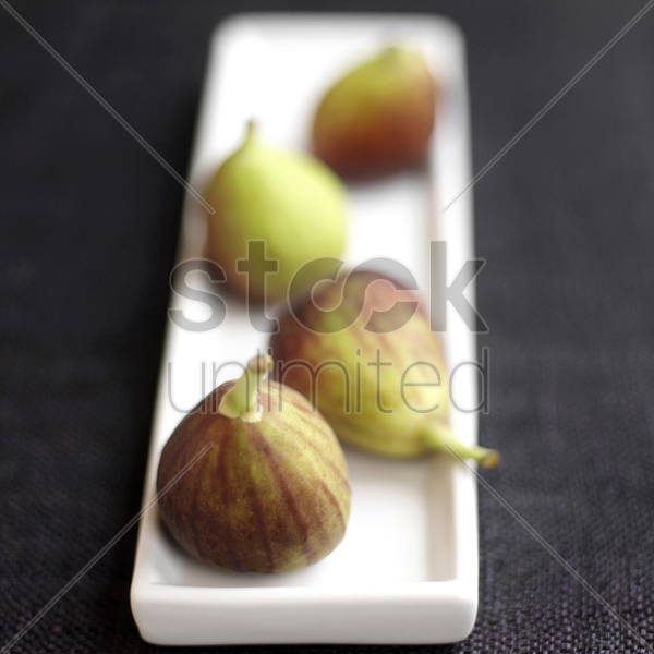close up of four figs on a small plate stock photo