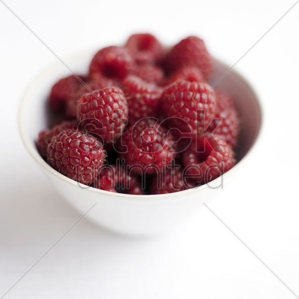 close up of some raspberries in a bowl stock photo