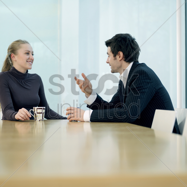 colleagues chatting leisurely stock photo