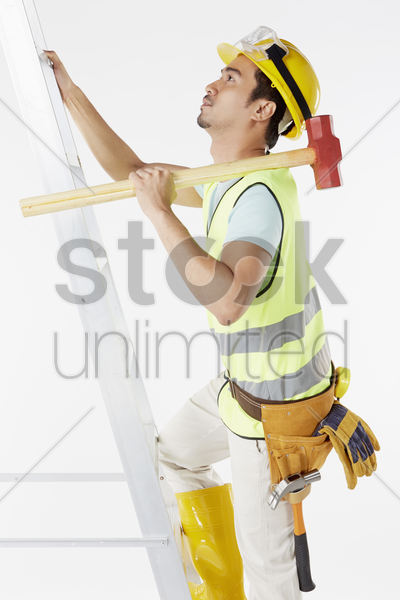 construction worker climbing up a ladder stock photo