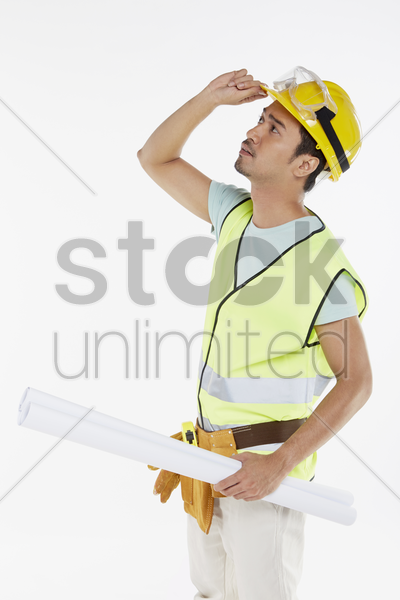construction worker holding a construction plan, looking around stock photo
