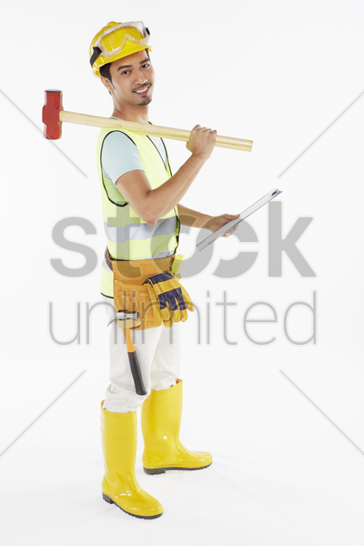 construction worker holding a hammer and clip file stock photo