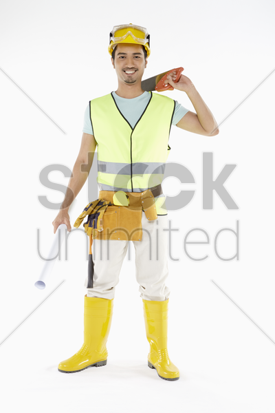 construction worker holding a saw and construction plan stock photo