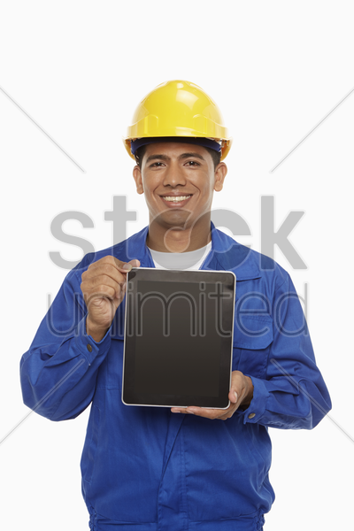 construction worker holding up a digital tablet stock photo
