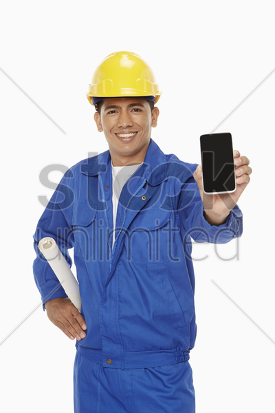 construction worker holding up a mobile phone stock photo