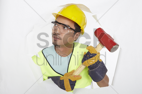 construction worker knocking wall with a hammer stock photo