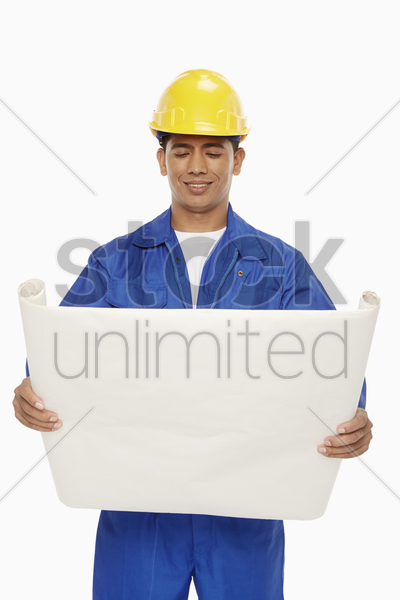 construction worker looking at a blueprint plan stock photo