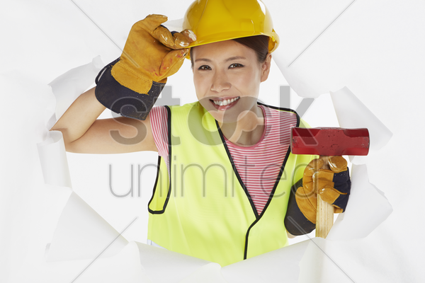 construction worker looking through a hole on the wall stock photo