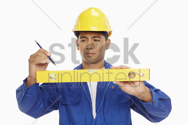 construction worker measuring with a spirit level stock photo