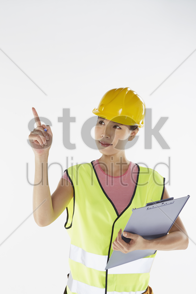 construction worker pointing while holding a clip file stock photo