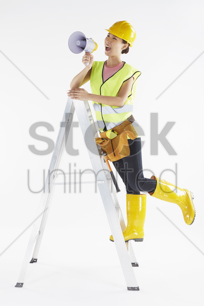 construction worker shouting into megaphone stock photo
