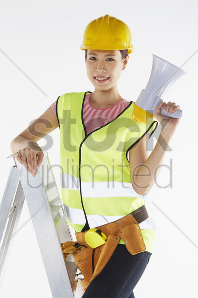 construction worker standing on a ladder, holding megaphone stock photo