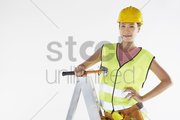 construction worker standing on ladder, holding a hammer stock photo