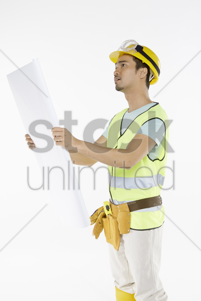 construction worker studying the construction plan stock photo