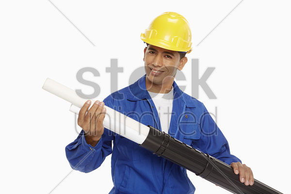 construction worker taking out blueprint from tube stock photo